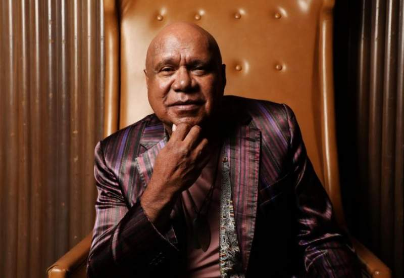 Archie Roach sits on a leather chair