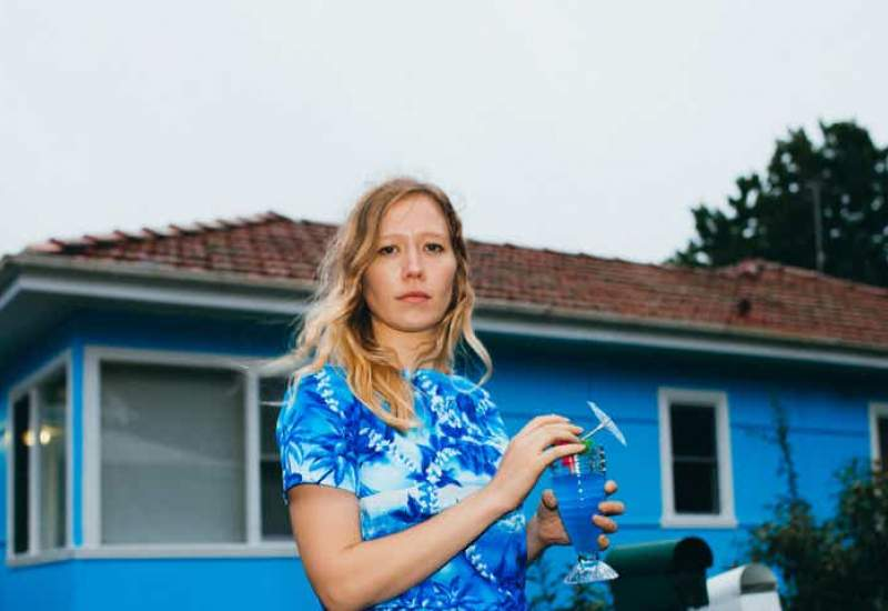 Julia Jacklin wears a blue shirt in front of a blue house